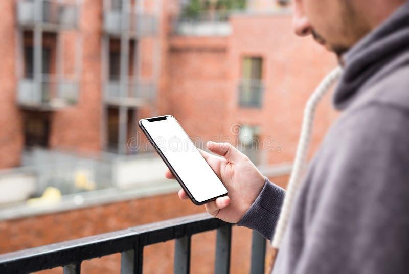 Homem que usa a moldura móvel moderna do smartphone menos projeto Disparado com opinião da terceiro-pessoa, tela vazia imagens de stock