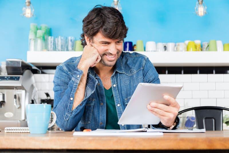 Homem que usa o assento ocasional do sorriso do homem de negócios do tablet pc fotografia de stock