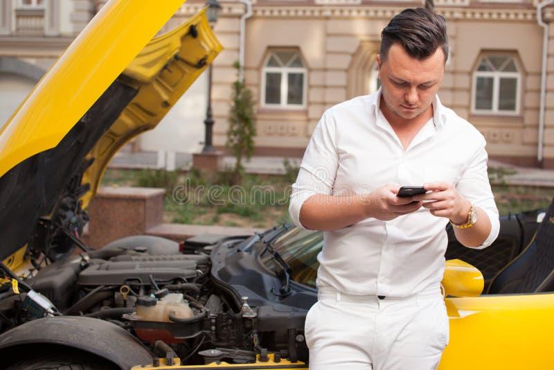 Homem que usa o carro próximo danificado do smartphone foto de stock