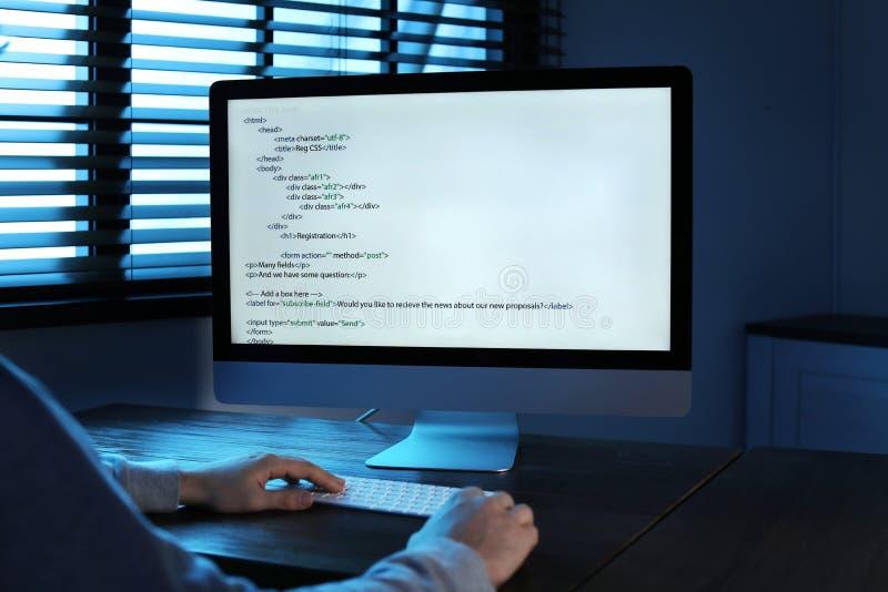 Homem que usa o computador na sala escura Ofensa criminosa imagens de stock royalty free