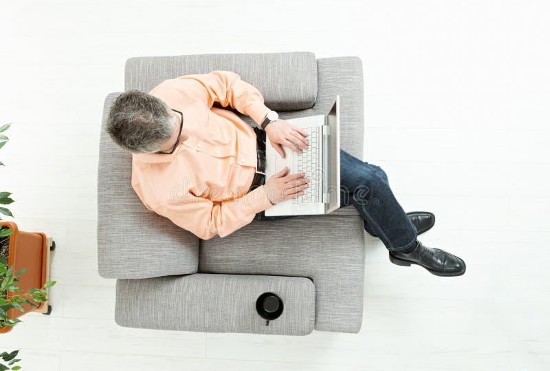 Homem que usa o computador portátil imagem de stock