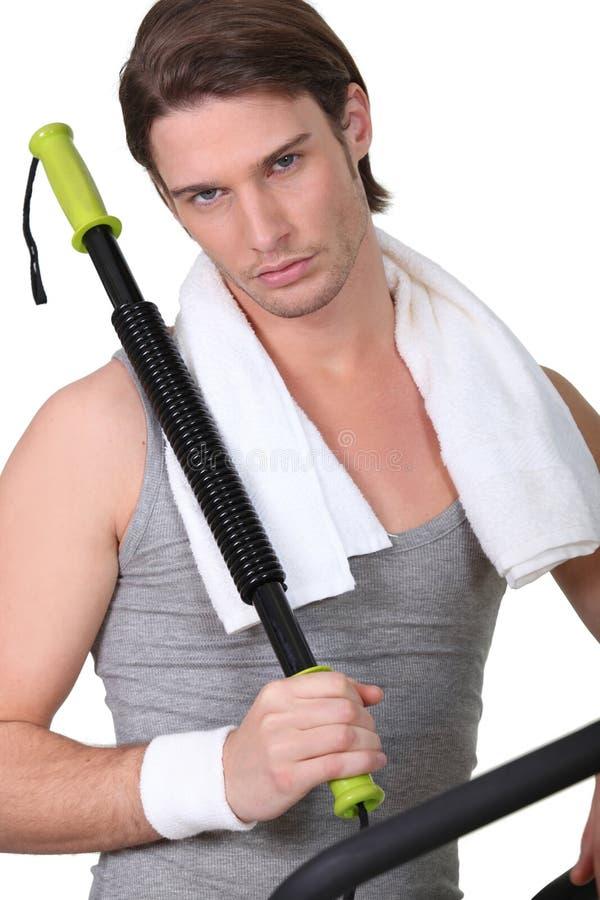 Homem que usa o equipamento do gym imagens de stock royalty free