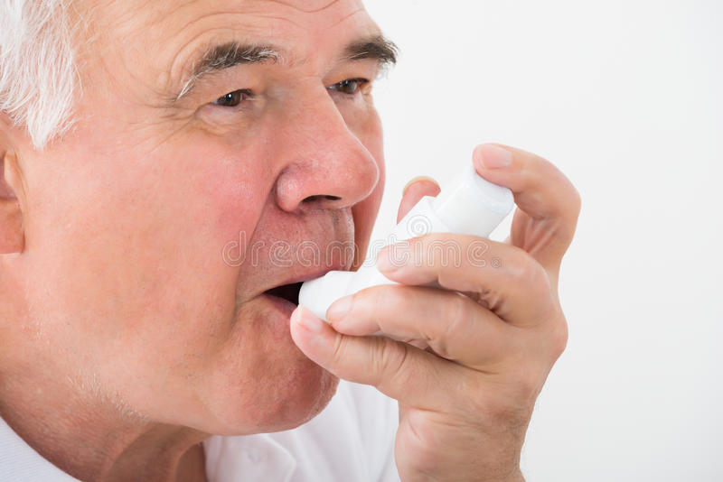 Homem que usa o inalador da asma imagens de stock