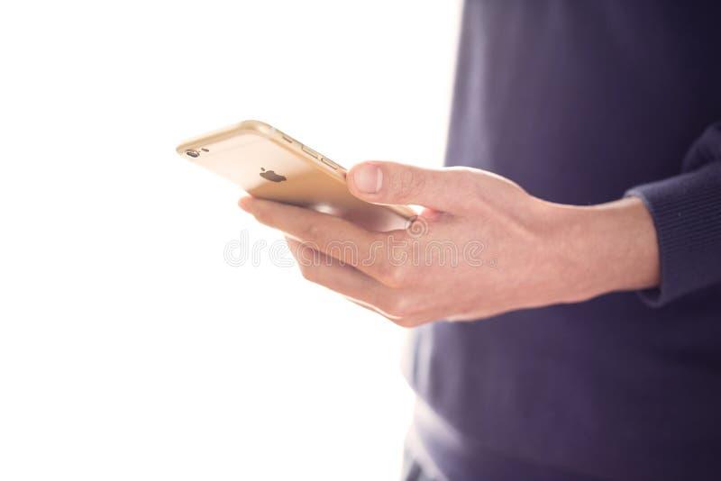 Homem que usa o iPhone 6 do ouro foto de stock