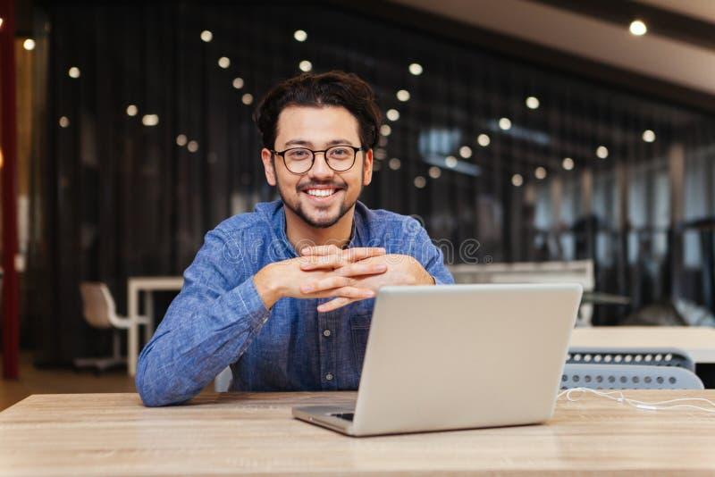 Homem que usa o laptop no escritório fotografia de stock