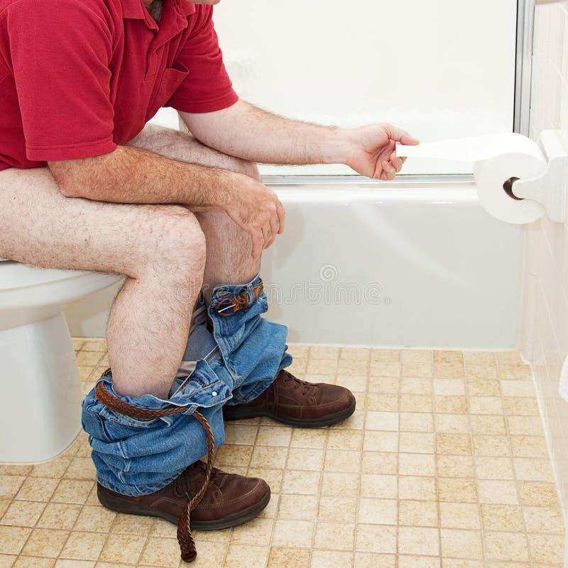 Homem que usa o papel higiênico no banheiro imagem de stock royalty free