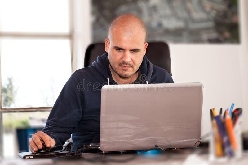 Homem que usa o portátil foto de stock