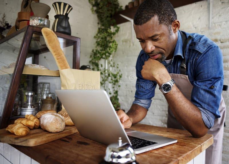 Homem que usa o portátil do computador fotografia de stock