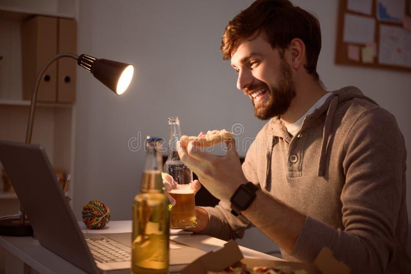 Homem que usa o portátil e comendo a pizza imagens de stock royalty free