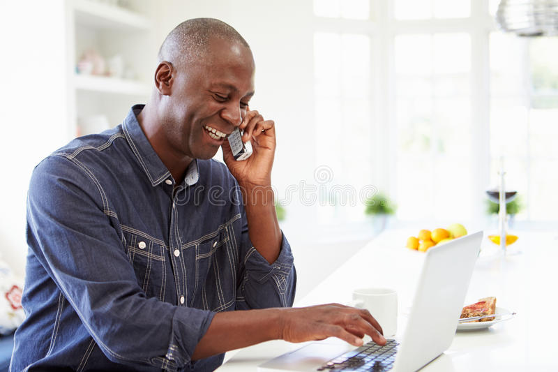 Homem que usa o portátil e falando no telefone na cozinha em casa