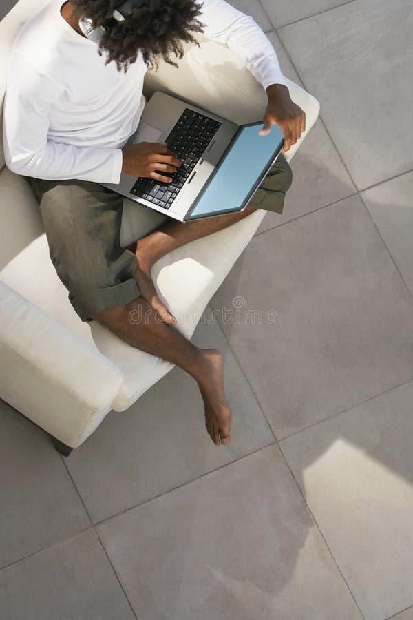 Homem que usa o portátil e a música de escuta no sofá imagem de stock royalty free