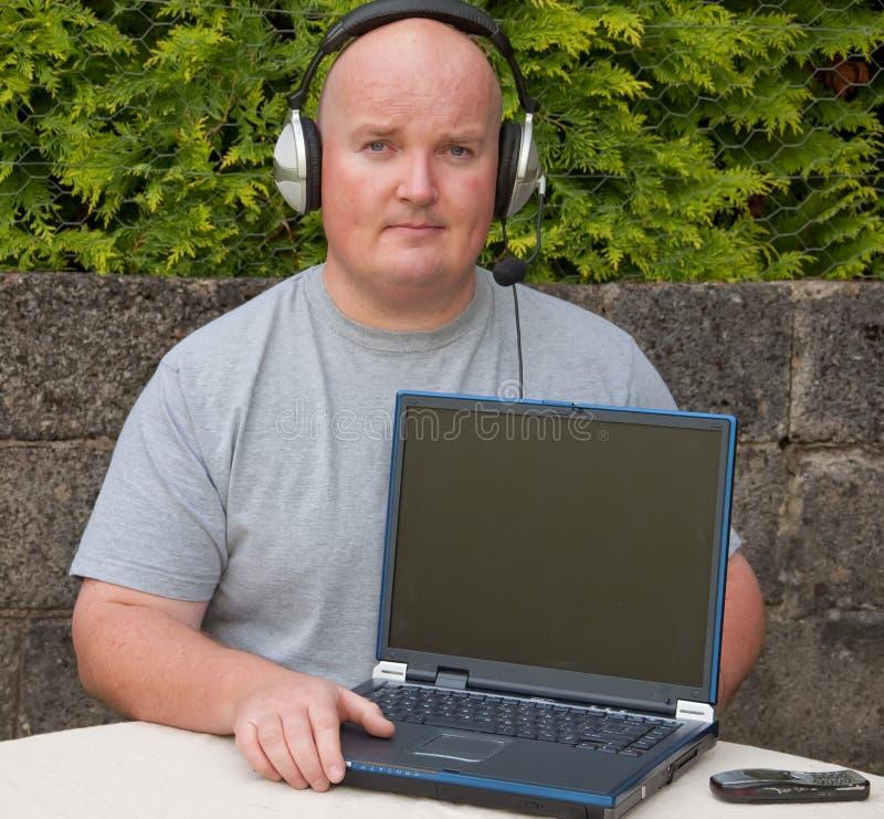 Homem que usa o portátil e o voip fotos de stock royalty free