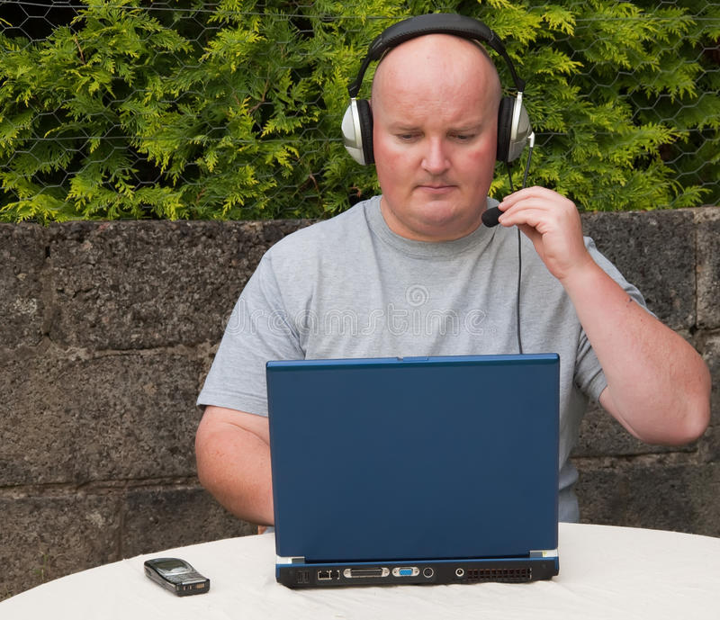 Homem que usa o portátil e o voip imagens de stock