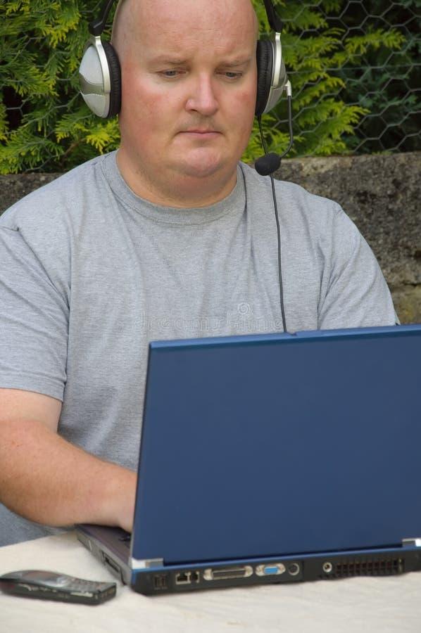 Homem que usa o portátil e o voip fotografia de stock royalty free