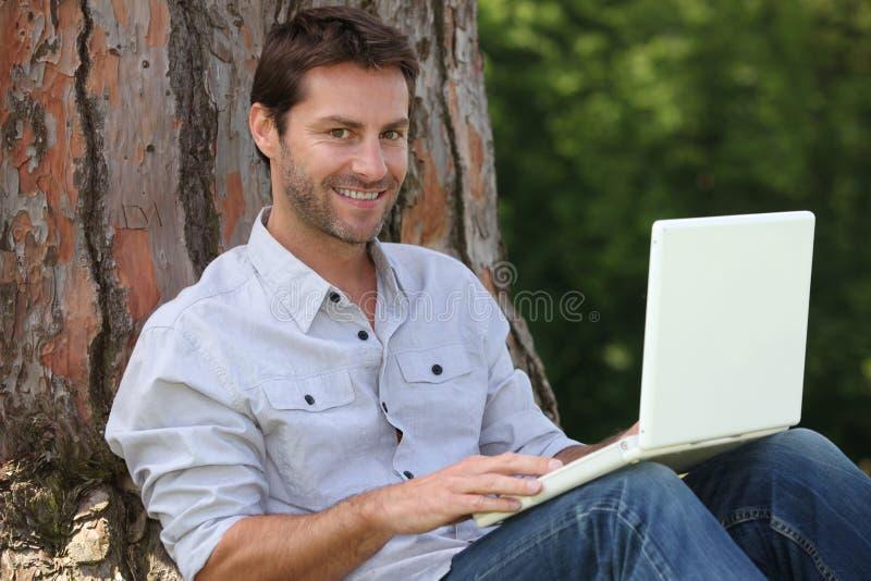 Homem que usa o portátil fora imagem de stock