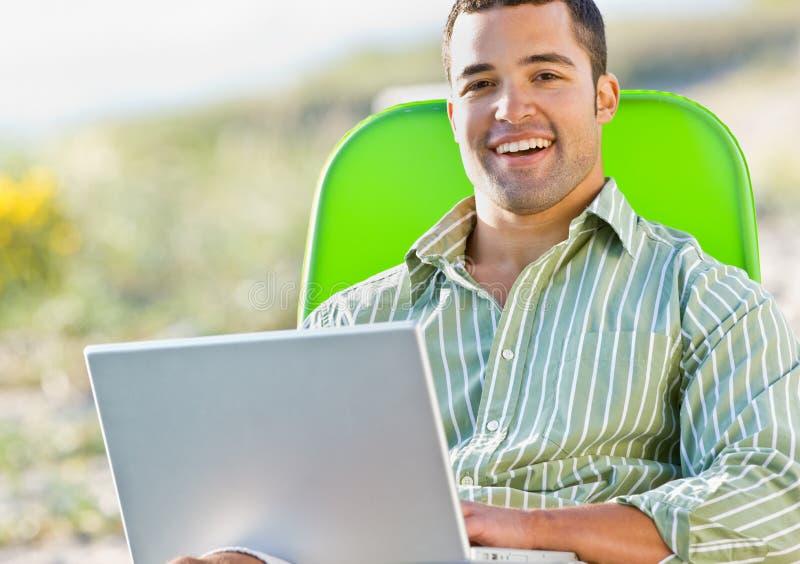 Homem que usa o portátil na praia imagens de stock royalty free