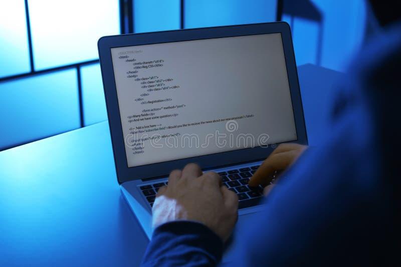 Homem que usa o portátil na tabela na sala escura Ofensa criminosa imagens de stock royalty free