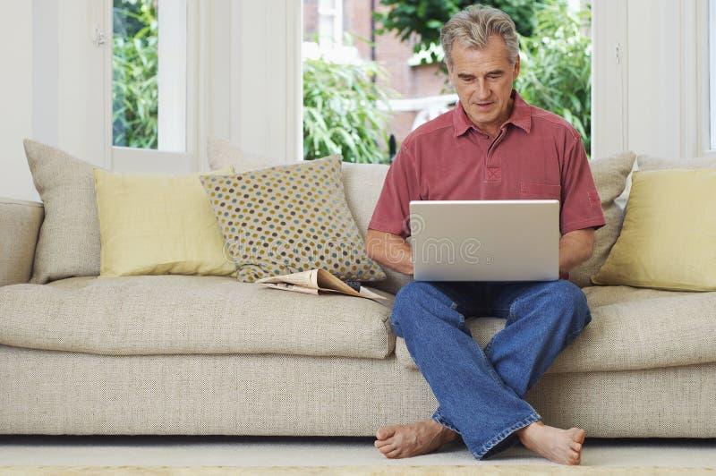 Homem que usa o portátil no sofá imagem de stock