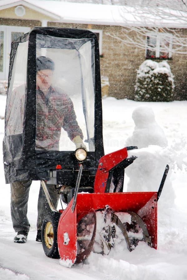 Homem que usa o snowblower fotografia de stock royalty free