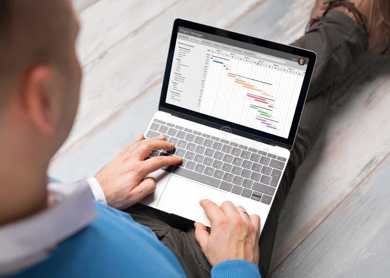 Homem que usa o software da gestão do projeto no laptop fotos de stock royalty free
