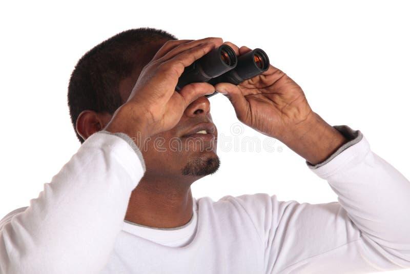 Homem que usa o spyglass foto de stock