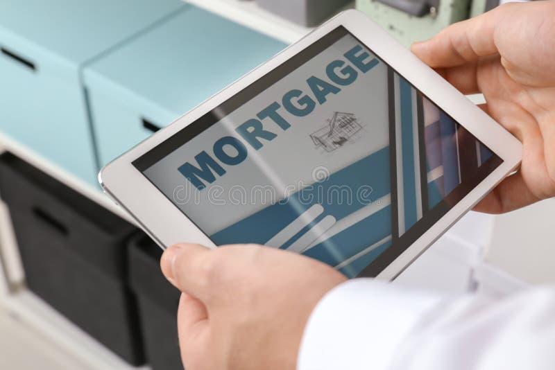 Homem que usa o tablet pc para pagar o empréstimo hipotecário em linha no escritório, close up imagem de stock royalty free