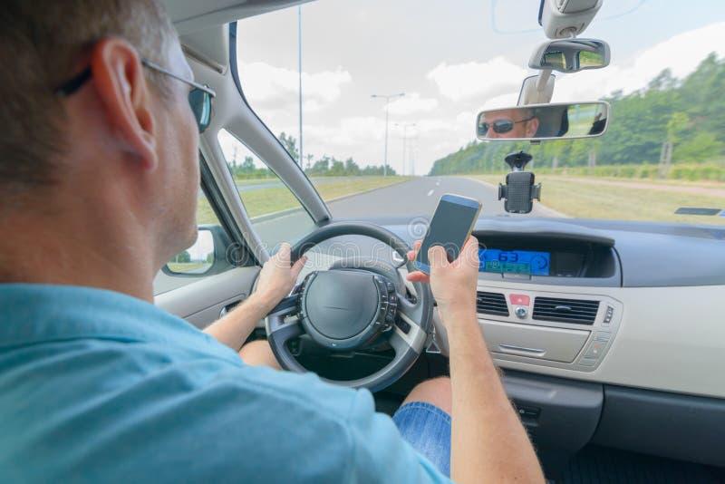 Homem que usa o telefone ao conduzir o carro imagens de stock