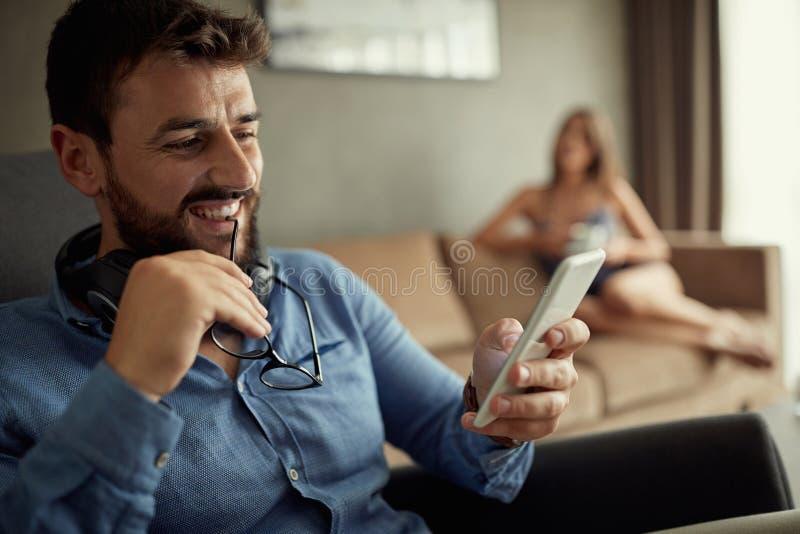 Homem que usa o telefone ao sentar-se no sofá em sua casa moderna Conceito dos jovens que trabalham dispositivos móveis imagens de stock