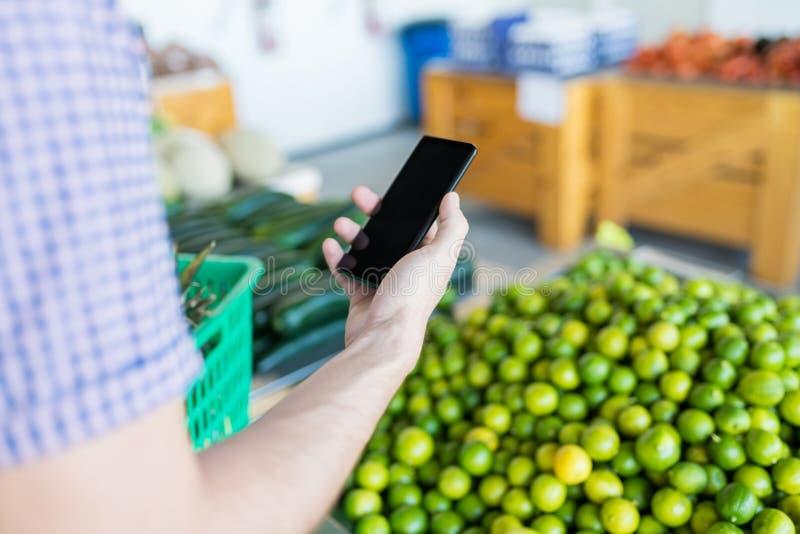 Homem que usa o telefone celular ao comprar o limão foto de stock royalty free