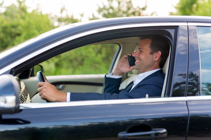 Homem que usa o telefone celular ao conduzir imagem de stock