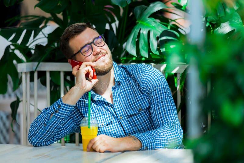 Homem que usa o telefone celular em um caf? imagens de stock