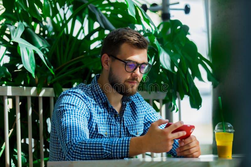 Homem que usa o telefone celular em um caf? fotos de stock
