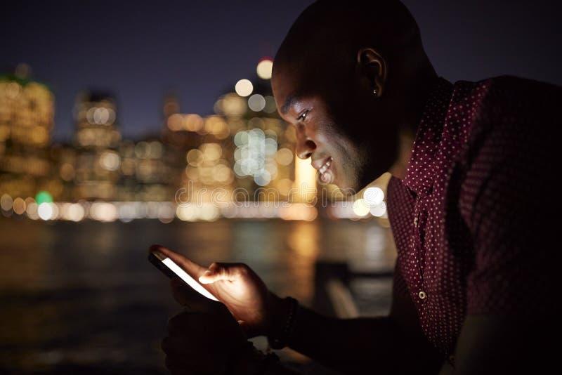 Homem que usa o telefone celular na noite com skyline da cidade no fundo fotografia de stock royalty free