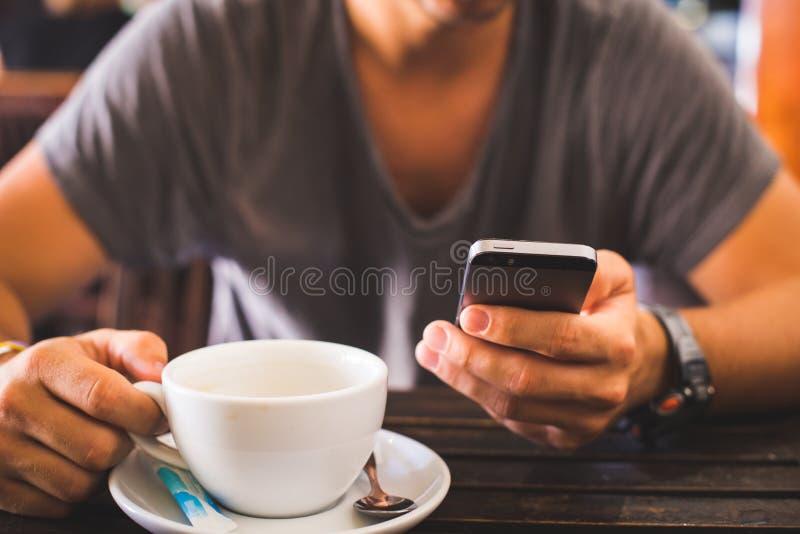 Homem que usa o telefone esperto e bebendo o café foto de stock royalty free