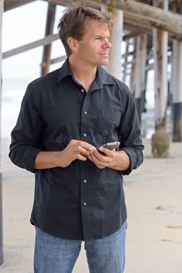 Homem que usa o telefone esperto na praia fotografia de stock royalty free