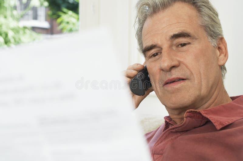Homem que usa o telefone celular e olhando Bill imagens de stock