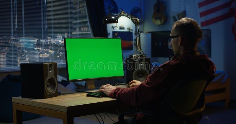 Homem que usa seu computador em casa imagens de stock