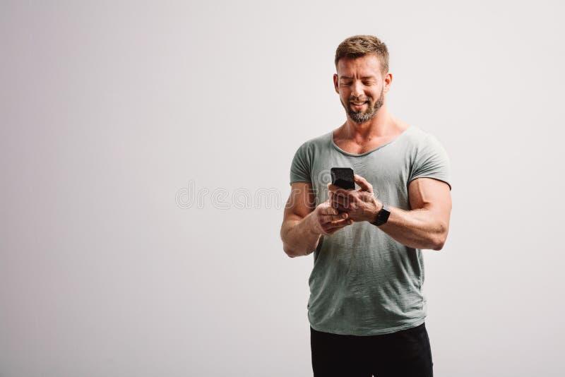 Homem que usa seu sorriso do smartphone imagem de stock