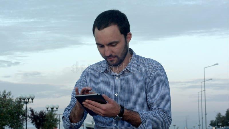 Homem que usa seu tablet pc fora no por do sol imagens de stock royalty free