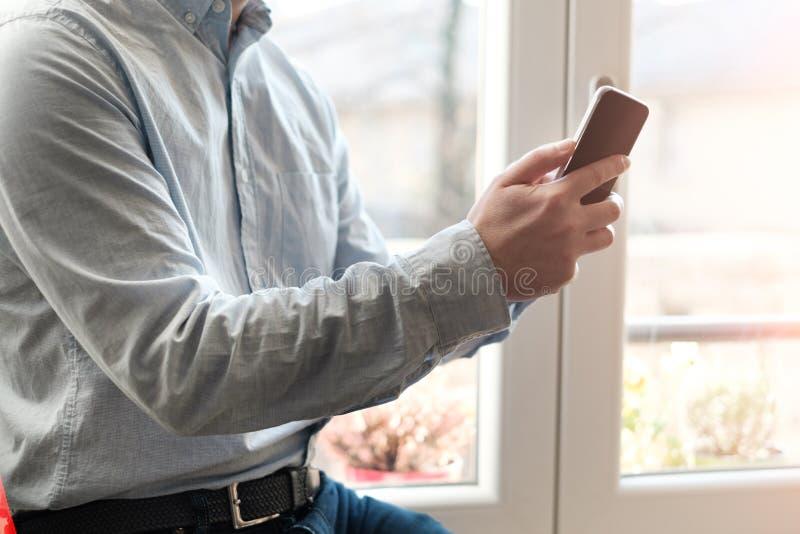 Homem que usa seu telefone celular em casa imagens de stock