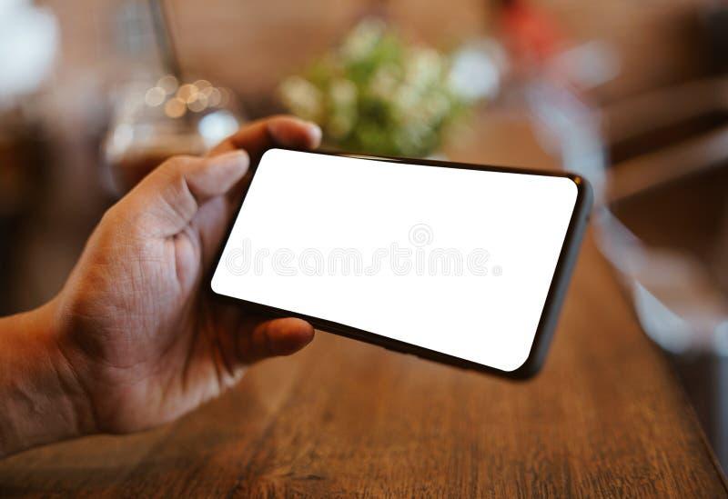 Homem que usa Smartphone na cafetaria Telefone celular da tela vazia para a montagem da exposi??o gr?fica fotos de stock royalty free