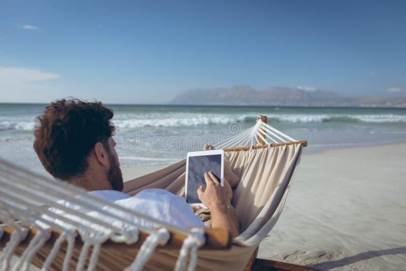 Homem que usa a tabuleta digital ao encontrar-se na rede na praia imagem de stock royalty free