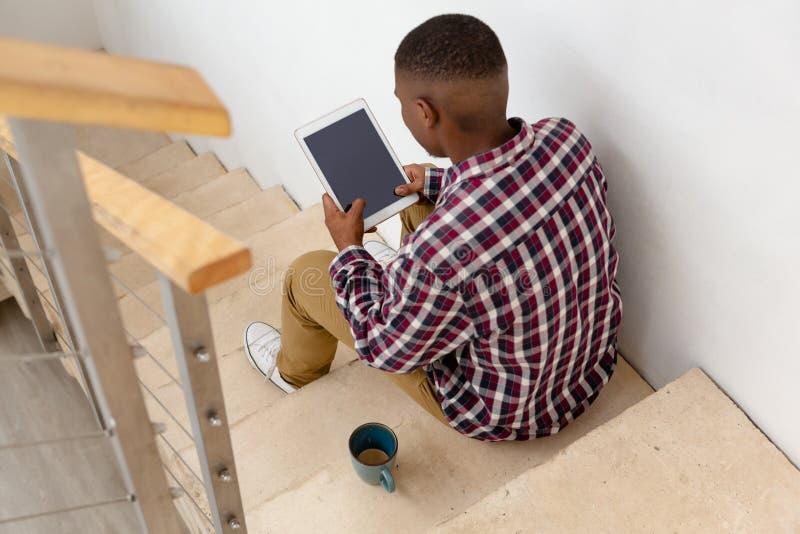 Homem que usa a tabuleta digital ao sentar-se em escadas em uma casa confortável fotografia de stock