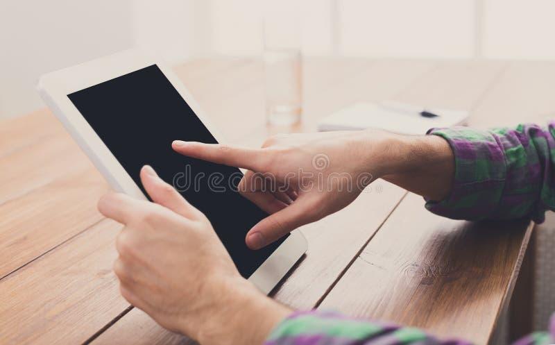 Homem que usa a tabuleta digital, fim acima, vista lateral, fotografia de stock royalty free