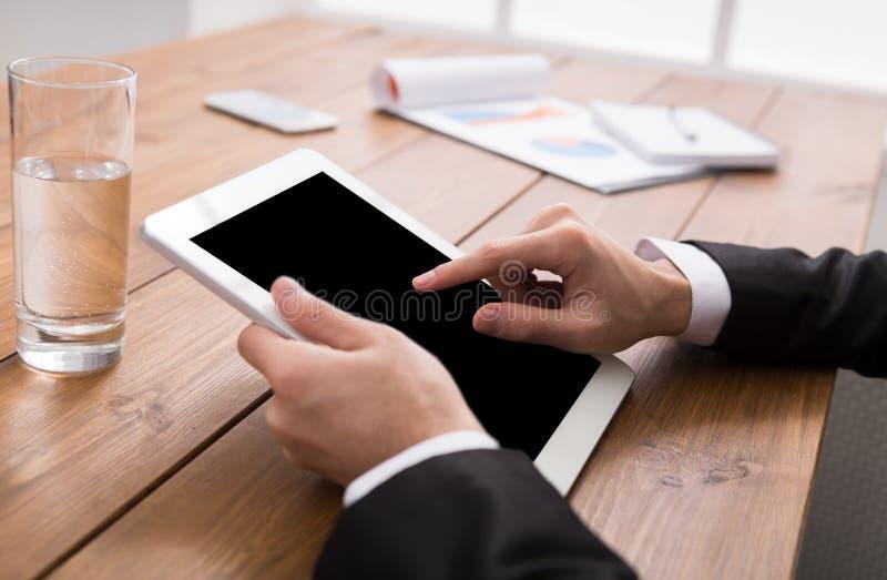 Homem que usa a tabuleta digital, fim acima, vista lateral, imagens de stock