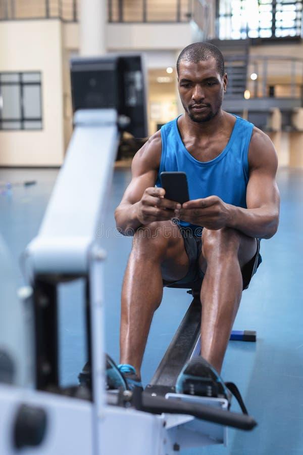Homem que usa telefone celular durante exercício em máquina de remar no ginásio fotografia de stock royalty free