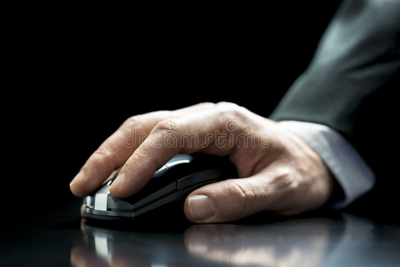 Homem que usa um rato sem corda do computador fotografia de stock