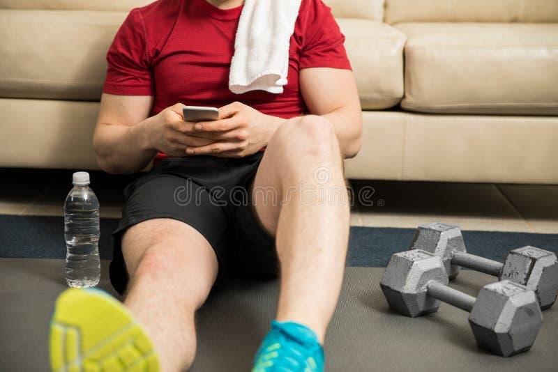 Homem que usa um smartphone ao exercitar foto de stock