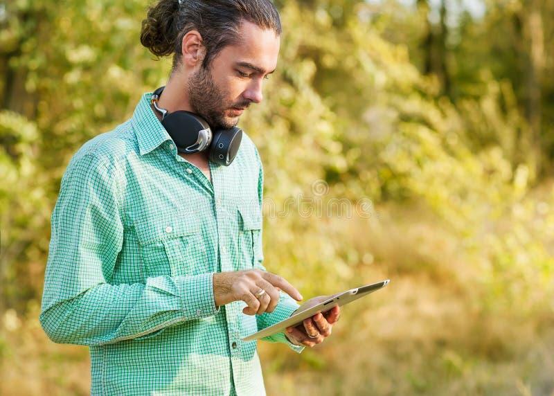 Homem que usa um tablet pc ao relaxar fotografia de stock royalty free