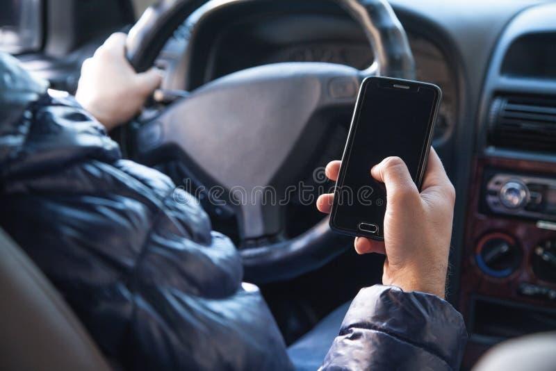 Homem que usa um telefone ao conduzir um carro imagens de stock royalty free